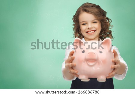 people, money, finances and savings concept - happy girl holding piggy bank over green chalk board background