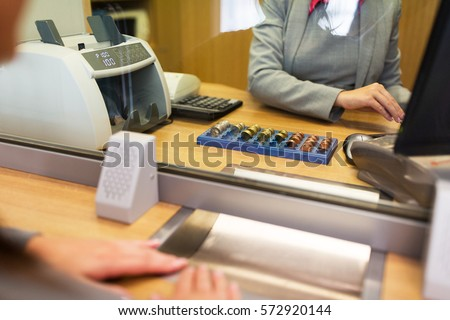 people, money, saving and finance concept - clerk counting coins for customer at bank office or currency exchanger Stock foto ©