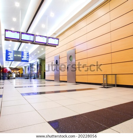 People mooving in hall corridor with tv displays in airport