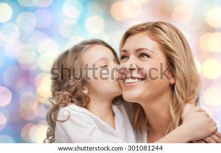 people, motherhood, family and adoption concept - happy mother and daughter hugging and kissing over blue holidays lights background