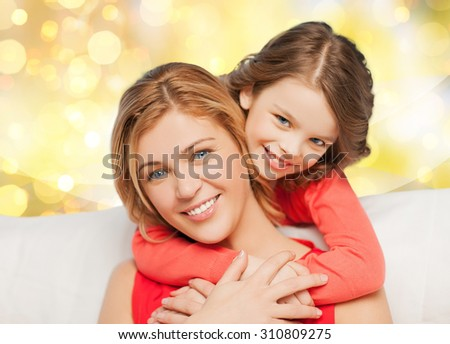 people, motherhood, family, holidays and adoption concept - happy mother and daughter hugging over yellow lights background