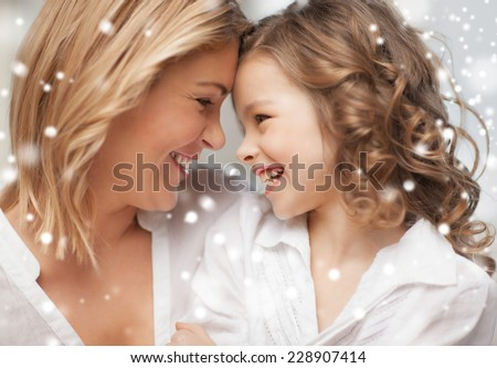 people, motherhood, family, winter and adoption concept - happy mother and daughter cuddling at home