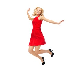 people, motion, happiness and holidays concept - happy young woman in red dress jumping high in air