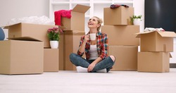 people, moving new place and repair concept   happy beautiful  young woman with many cardboard boxes sitting on floor with Cup at home