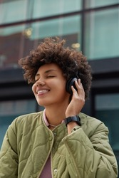 People music and lifestyle concept. Pleased carefree lovely teenage girl keeps eyes closed enjoys favorite melody in wireless headphones smiles broadly dressed in jacket smartwatch on wrist.