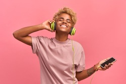 People, music, emotions concept. Delighted carefree female with Afro hairstyle dances in rhythm of melody, closes eyes listen to loud song in headphones, holds smartphone has fun. Pink color prevails