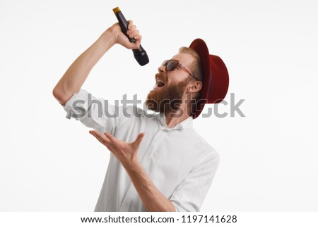 People, music, fun, show and entertainment concept. Studio shot of emotional handsome stylish red haired pop artist with thick beard singing in microphone wearing red round hat and trendy shades