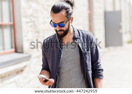 people, music, technology, leisure and lifestyle - man with earphones and smartphone walking in city