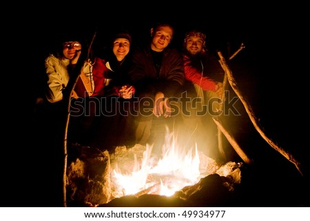 People near campfire in forest