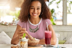 People, nutrition and lifestyle concept. Glad cheerful black lady eats delicious dish with wooden spoon in cafeteria, drinks cocktail, has smile on face, likes local cuisine, has rest in exotic place