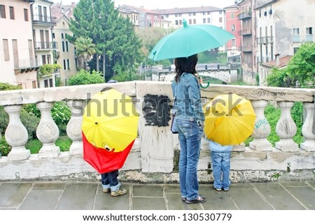 people of a family under the umbrella during a rainy day