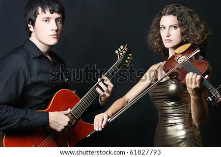 People of entertainment and performance. Portrait of musical couple, man guitarist and woman violinist on black