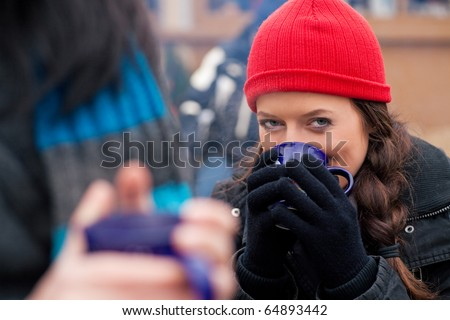 People on a Christmas market drinking punch or hot spiced wine, it is cold and they have a need to warm up