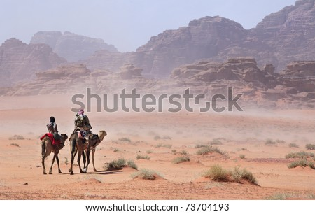 People on camels going through the desert storm
