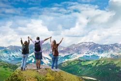 People on  hiking trip. Happy family on top of  beautiful  mountain holding  raised hands . View from Trail Ridge Road. Rocky Mountains National Park, Colorado.USA.