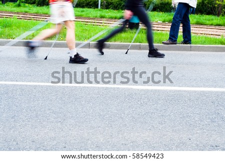 People on nordic walking race on city streets