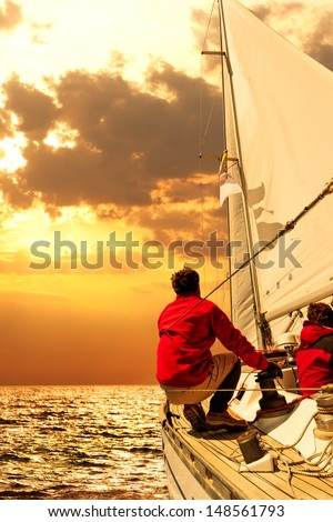 People on sailing boat in the sea at sunset