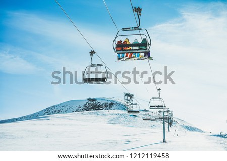 People on ski lift in winter ski resort - Holidays, snow gear renting, skiing, snowboarding and mountain landscape concept - Focus on guys sitting in cable car