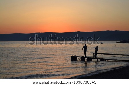 People on the background of a beautiful sunset on the lake