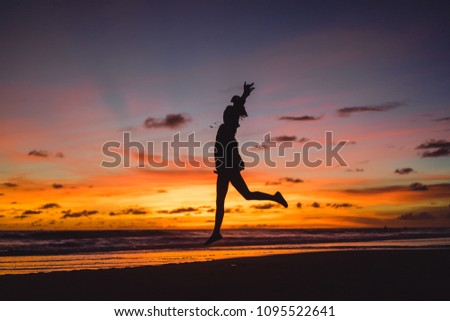 people on the beach at sunset. the girl is jumping against the backdrop of the setting sun. #1095522641