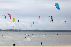 People on the beach practicing kitesurf