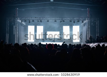People on the dance floor during a concert in a hangar. Five white led wall ideal to insert text or logos. Laser and lights illuminate the party. Wide view. Dj on the stage