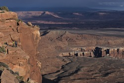 People on the edge of the cliff, looking down from the White Rim overlook in Canyonlands National Park, Utah, USA