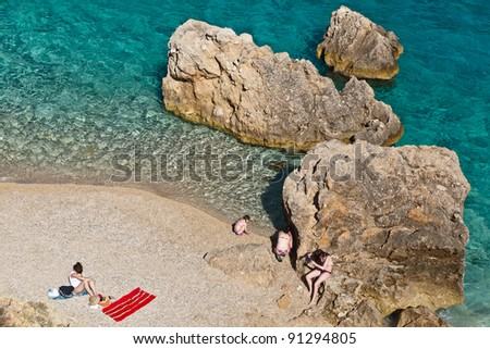 People on the Rocky Beach in Croatia - stock photo