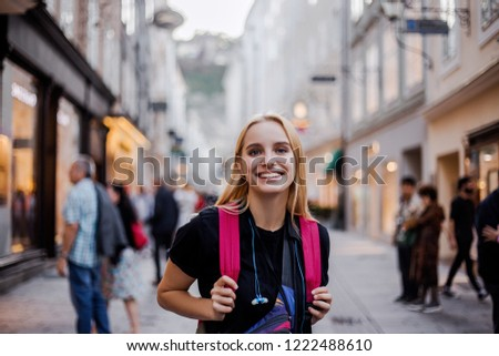 People on travel, photos on advertising tours. Happy smile traveler on a tour of Europe. Walking tour city tour. A woman received a visa at a travel agency and went on a weekend voyage. Evening light