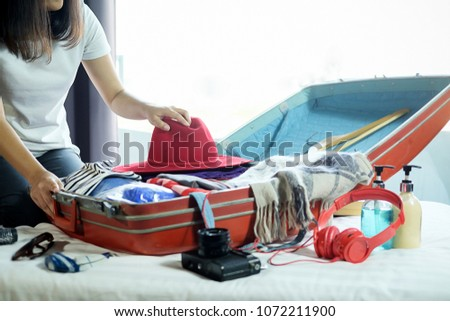 People packed suitcase with travel accessories on bed. Vacation concept #1072211900