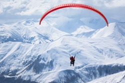 People paragliding tandem above mountain in winter in Georgia ski resort. Concept of active lifestyle and extreme sport adventure.