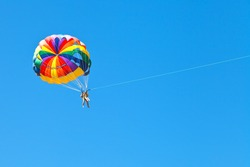 people parascending on parachute in blue sky in summer day