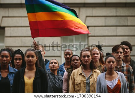 People participate in the pride parade. Multi-ethnic people in the city street with a woman waving gay rainbow flag.