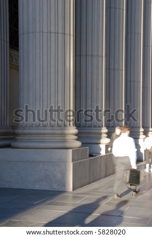 People passing by a bank in front of the ionic columns. Can also be a courthouse, university, etc.