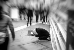 People passing indifferently next to beggar in the street of the modern city