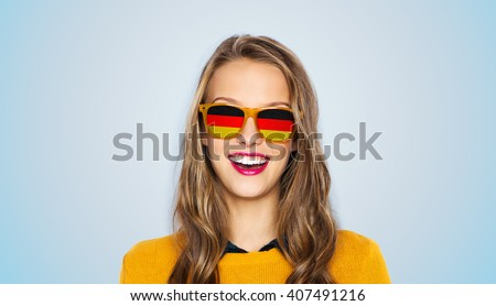 people, patriotism and nationality  concept - happy young woman or teen girl face in sunglasses with german flags over blue background ストックフォト ©