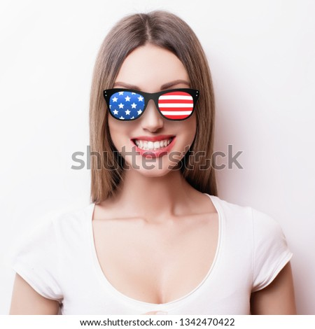 People, patriotism, national pride and independence day concept - happy teenage girl in sunglasses with american flag #1342470422