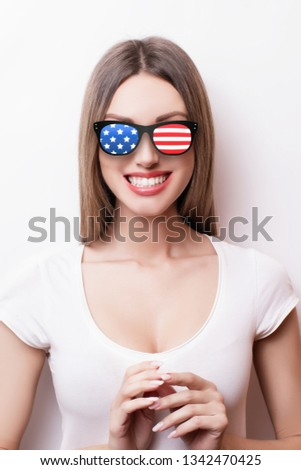 People, patriotism, national pride and independence day concept - happy teenage girl in sunglasses with american flag #1342470425