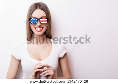 People, patriotism, national pride and independence day concept - happy teenage girl in sunglasses with american flag #1342470428