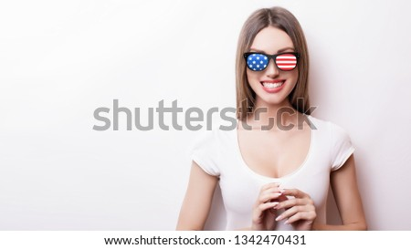 People, patriotism, national pride and independence day concept - happy teenage girl in sunglasses with american flag #1342470431