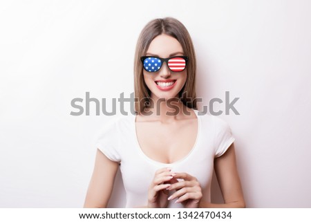 People, patriotism, national pride and independence day concept - happy teenage girl in sunglasses with american flag #1342470434