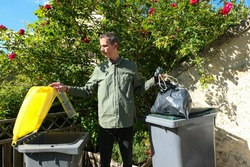People performing a selective sorting of household waste in recycling bins. Man putting plastic bottles in a yellow container and garbage in a bag in a green container.