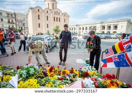 People place flowers and light candles in commemoration of the victims of Malaysia Airlines MH17 plane accident in eastern Ukraine, in front of the Dutch embassy in Kiev, Ukraine, 17 July 2015.