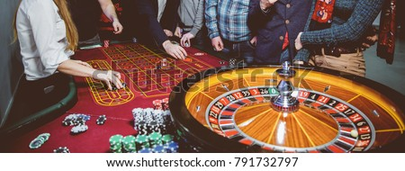 People play poker roulette at the table. Friends playing in the casino. A group of young people at a roulette table with a tape measure. Gambling. Vintage photo processing / black and white photo