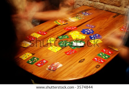 People playing a fast game of cards around a wooden table next to a stone wall