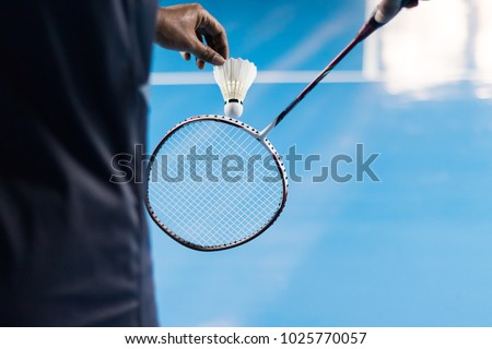 People Playing Badminton, Badminton is served on court blue background.