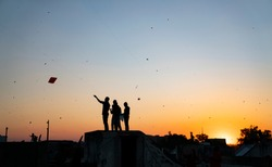 People playing kites in the rooftop during sunset