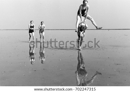 People playing leapfrog on beach