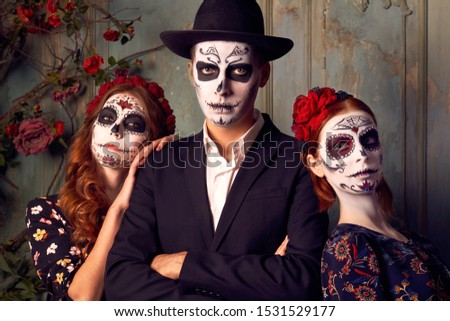 People preparing for carnival, dressed in costume. Day of dead. Zombie portrait. Studio shot of serious threes wears vivid makeup, celebrate traditional mexican holiday, wear wreath made of flowers