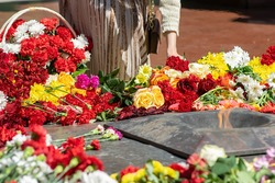 people present put flowers at the eternal flame on the memorial to the victims, dead soldiers